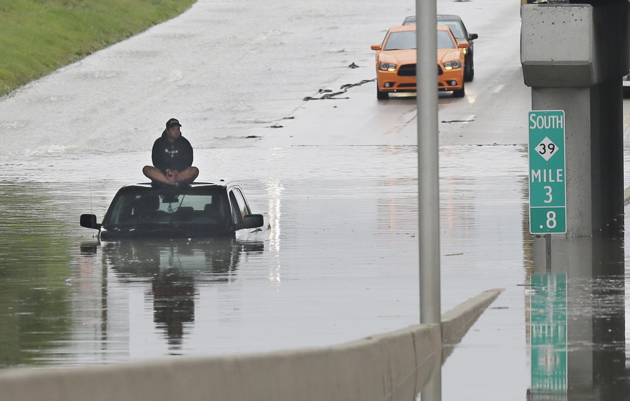 A stranded motorist sits on top his car as he awaits rescue from the flooded Southfield Freeway, Monday, Aug. 11, 2014, in Dearborn, Mich. The Michigan State Police issued an advisory Monday evening, urging drivers to avoid non-essential use of all metro Detroit freeways after heavy rain and thunderstorms left roads flooded and impassable. Interstate 75 at I-94 in Detroit has been shut down in both directions, according to the Michigan Department of Transportation. (AP Photo/Carlos Osorio)