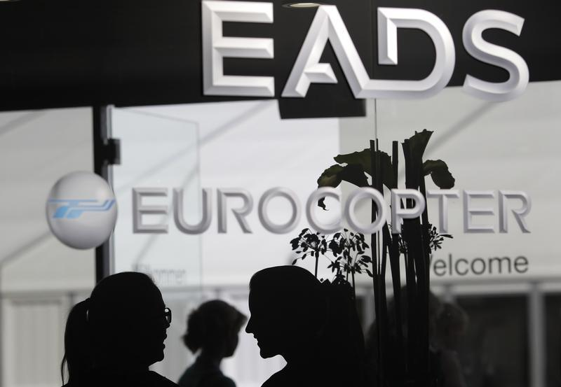 Visitors talk near the welcome desk of the EADS booth at the ILA Berlin Air Show south of Berlin