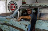 Julio Alvarez, co-owner of Nostalgicar, poses inside his latest classic American car acquisition that he hopes to restore in Havana, Cuba, Wednesday, Oct. 21, 2020. Alvarez and his business partner met with influential Republican Cuban American lawmakers during a 2017 trip to Washington in which they advocated for U.S.-Cuba relations to continue. (AP Photo/Ramon Espinosa)