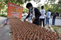 NEW DELHI, INDIA - AUGUST 4: A worker arranges diyas or earthen lamps which were distributed by BJP MP Parvesh Verma outside his official residence on the eve of the foundation stone laying in Ayodhya of the Ram Temple, on August 4, 2020 in New Delhi, India. Prime Minister Narendra Modi will on Wednesday attend a public function on laying of the foundation stone of 'Shree Ram Janmabhoomi Mandir' at Ayodhya. Ram Janmabhoomi Teerth Kshetra, the trust set up for the construction and management of Ram temple, has invited 175 eminent guests for the foundation stone-laying ceremony after personally discussing with BJP veterans L K Advani and Murli Manohar Joshi, lawyer K Parasaran and other dignitaries. (Photo by Mohd Zakir/Hindustan Times via Getty Images)