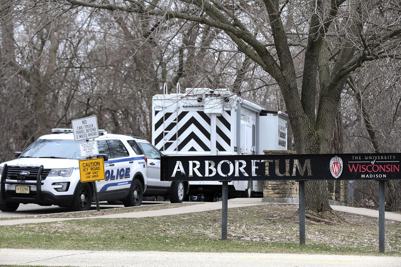Vehicles from the Madison Police Department, Dane County Sheriff's Office and the University of Wisconsin Police Department are stationed outside the UW-Arboretum in Madison, Wis. as law enforcement personnel investigate a double homicide Tuesday, March 31, 2020. (John Hart/Wisconsin State Journal via AP)