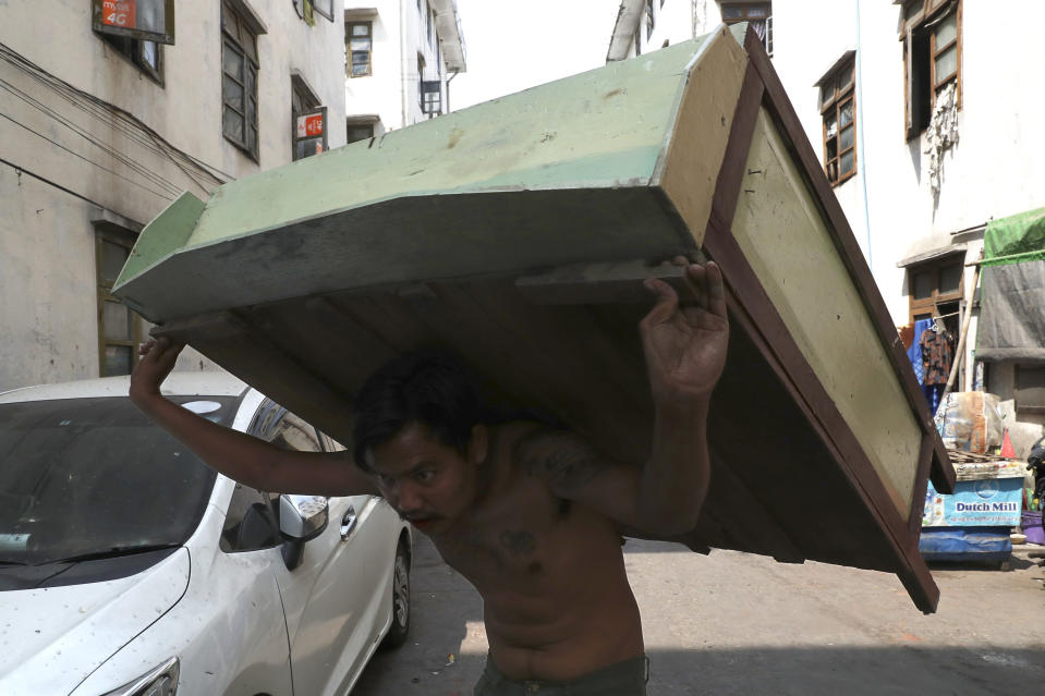 A state railway employee carries a piece of furniture after being evicted from his home Saturday, March 20, 2021, in Mandalay, Myanmar. State railway workers in Mandalay have been threatened with eviction to force them to end their support for the Civil Disobedience Movement (CDM) against military rule. (AP Photo)