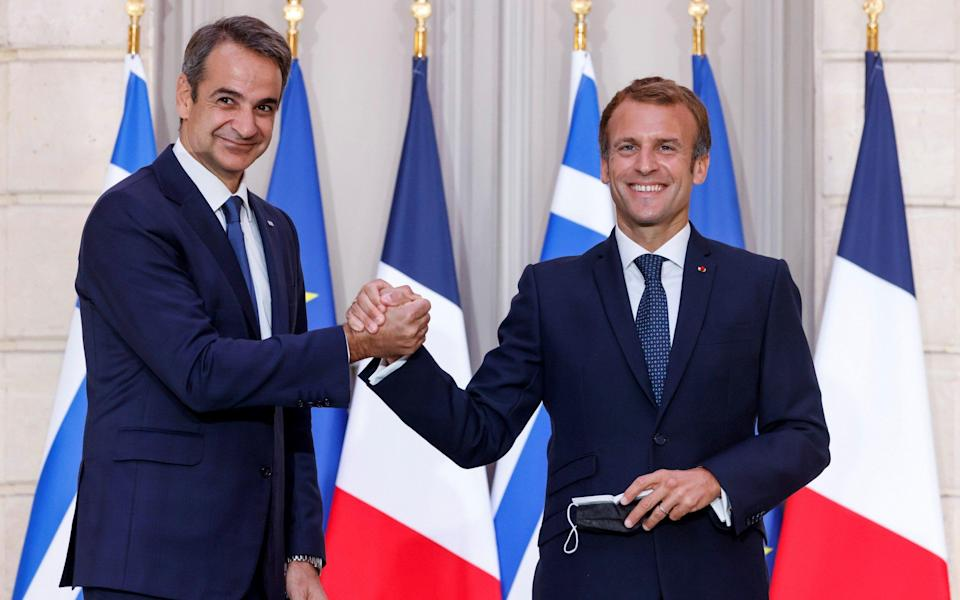 Greek prime minister Kyriakos Mitsotakis (L) shakes hands with French President Emmanuel Macron at the Elysee Palace - Shutterstock