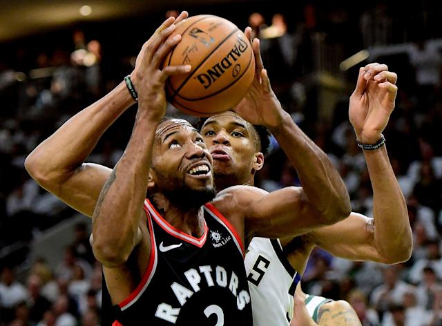 Milwaukee Bucks forward Giannis Antetokounmpo (34) tries to stop Toronto Raptors forward Kawhi Leonard (2) as he looks for the shot during the second half in Game 1 of the NBA basketball playoffs Eastern Conference final in Milwaukee on Wednesday, May 15, 2019. (Frank Gunn/The Canadian Press via AP)