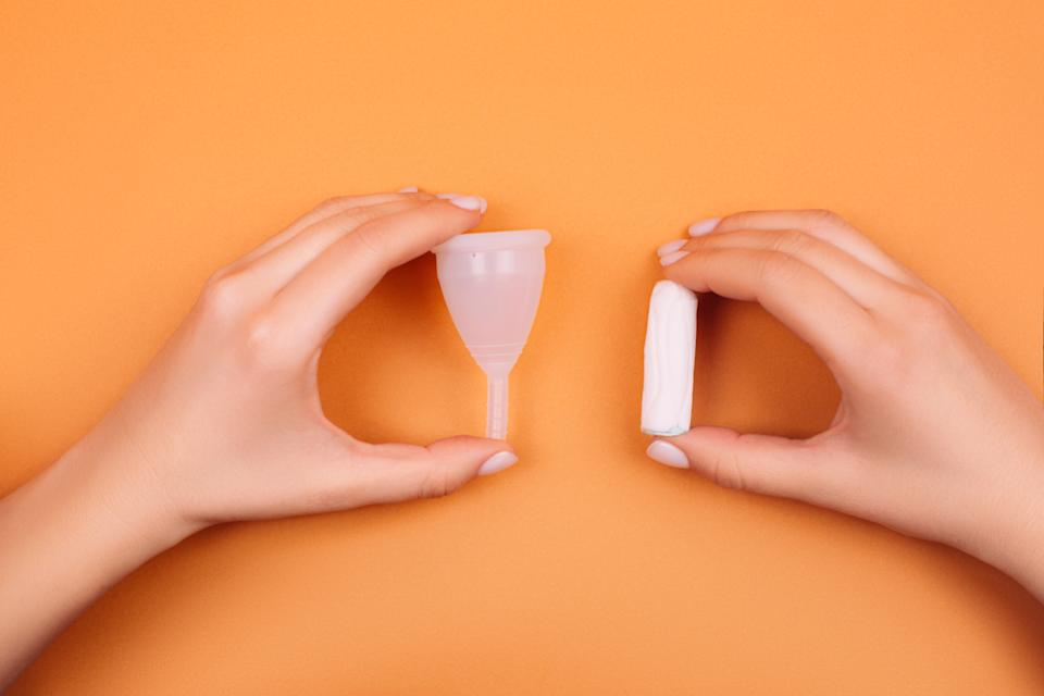Reusable menstrual cup or disposable tampon . Care for woman's hygien a coral background. Flat lay style,