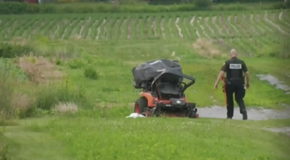 Emergency worker stands next to a ride-on lawn mower in an empty field.