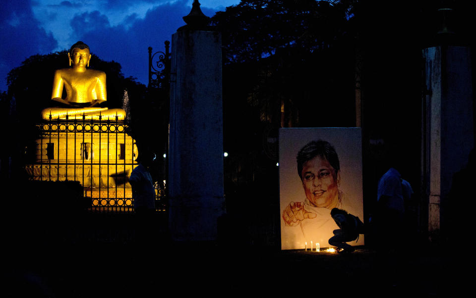 FILE - In this Tuesday, Jan. 8, 2013, file photo, family members and friends light candles next to a portrait of slain newspaper editor Lasantha Wickrematunge, on his fourth death anniversary in Colombo, Sri Lanka. The daughter of the slain journalist filed a complaint Friday, Jan. 8, 2021, with the United Nations Human Rights Committee over alleged government involvement in her father's death 12 years ago. The San Francisco-based Center for Justice and Accountability filed the complaint on behalf of Ahimsa Wickrematunge, the daughter of Lasantha, who was allegedly killed by a military-linked hit squad while driving to work on Jan. 8, 2009. (AP Photo/Gemunu Amarasinghe, File)