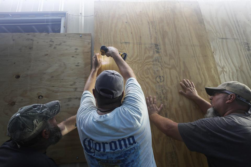 LAKE  CHARLES, LOUISIANA - OCTOBER 08: Local volunteers help board up a business ahead of Hurricane Delta on October 8, 2020 in Lake Charles, Louisiana. Residents along the Gulf Coast are bracing for the arrival of Hurricane Delta which is expected to make landfall in Louisiana on October 9. (Photo by Mario Tama/Getty Images)