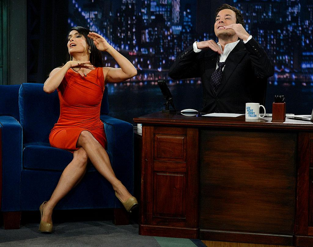 "NEW YORK, NY - OCTOBER 12:  Actress Salma Hayek Pinault helps host Jimmy Fallon with his tie during a taping of ""Late Night With Jimmy Fallon"" at Rockefeller Center on October 12, 2012 in New York City.  (Photo by Jason Kempin/Getty Images)"