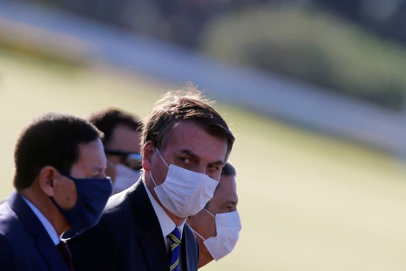 Brazil's President Jair Bolsonaro wearing a protective mask and other Brazil's ministers attend a national flag hoisting ceremony in front the Alvorada Palace, amid the coronavirus disease (COVID-19) outbreak in Brasilia