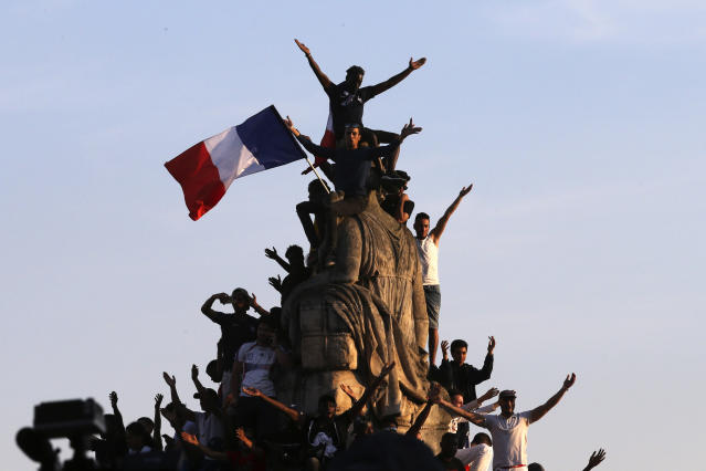 People wait on the Place de la Concorde for the French soccer team Monday, July 16, 2018 in Paris. Following a victory lap down the packed Champs-Elysees Avenue in an open air bus, the squad that defeated Croatia 4-2 in the tournament final on Sunday attended an informal garden party hosted by President Emmanuel Macron. (AP Photo/Bob Edme)