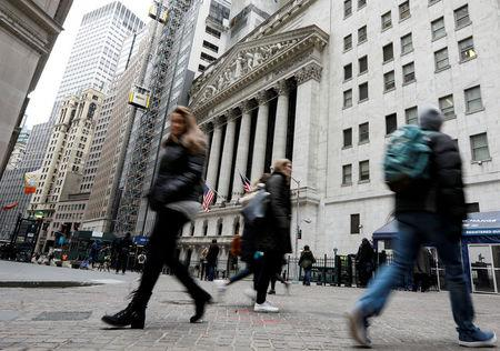 People walk on Wall St. in front of the NYSE in New York