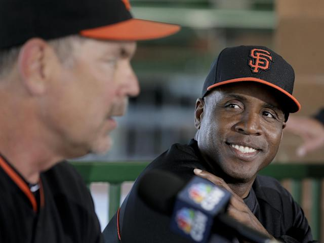 San Francisco Giants baseball team manager Bruce Bochy, left, joins former player Barry Bonds at a news conference before a spring training baseball game in Scottsdale, Ariz., Monday, March 10, 2014. Bonds starts a seven day coaching stint today. (AP Photo/Chris Carlson)