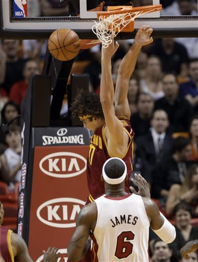 Cleveland Cavaliers' Anderson Varejao, of Brazil, dunks in front of Miami Heat's LeBron James (6) during the first half of an NBA basketball game, Tuesday, Jan. 24, 2012, in Miami. (AP Photo/Lynne Sladky)
