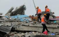 Police with sniffer dog inspect collapsed hospital building following earthquake in Mamuju