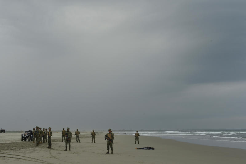 Security forces form a cordon around the lifeless body of Emmanuel Cheo Ngu, of Cameroon, on the shore of Boca Barra Beach, in Puerto Arista, Mexico, Friday, Oct. 11, 2019. The 39-year-old man was traveling with a group of people in a small boat when it overturned in the southern coast of Mexico, in the Pacific Ocean. Several passengers were rescued but a few remain missing. (AP Photo/Isabel Mateos)