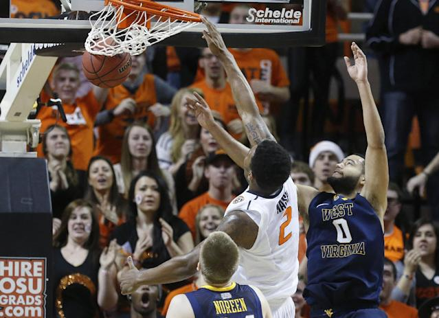 Oklahoma State wing Le'Bryan Nash (2) dunks in front of West Virginia forward Kevin Noreen (34) and forward Remi Dibo (0) in the first half of an NCAA college basketball game in Stillwater, Okla., Saturday, Jan. 25, 2014. Oklahoma State won 81-75.(AP Photo/Sue Ogrocki)