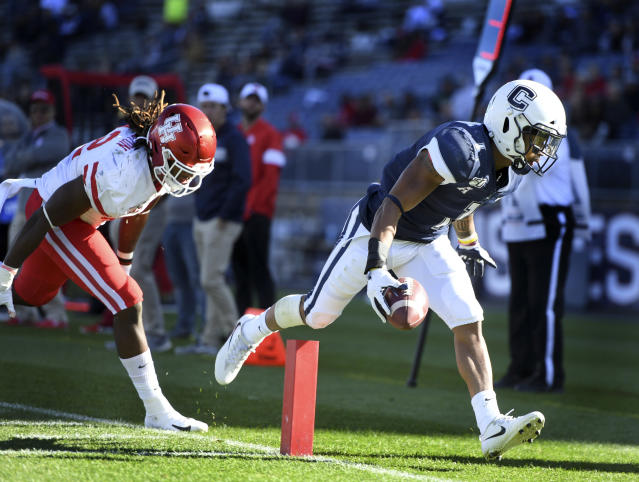 Connecticut running back Art Thompkins (1) scores being chased by Houston linebacker Terrance Edgeston (42) during the second half of an NCAA college football game Saturday, Oct. 19, 2019, in East Hartford, Conn. (AP Photo/Stephen Dunn)