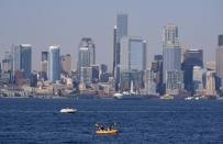 Kayakers and boaters ply the waters of Elliott Bay with the Seattle skyline behind during a heat wave hitting the Pacific Northwest, Sunday, June 27, 2021. The day before set a record high for the day with more record highs expected today and Monday. (AP Photo/John Froschauer)
