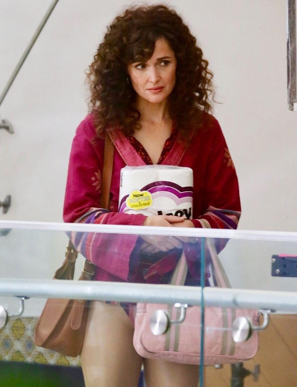 <p>Rose Byrne holds a package of toilet paper as she and costar Paul Sparks (not pictured) film scenes for <em>Physical</em> at a Los Angeles strip mall on Tuesday.</p>