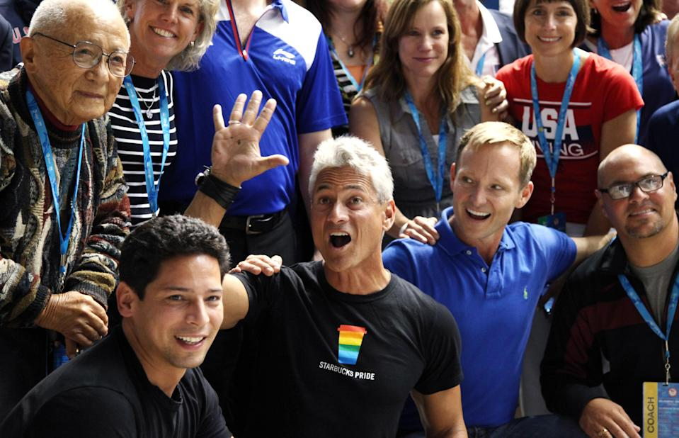 FILE - In this June 23, 2012, file photo, Former U.S. Olympian Greg Louganis, center, waves as he lines up for a group portrait with other Olympians at the U.S. Olympic diving trials in Federal Way, Wash. As an athlete mentor at the London Olympics, Louganis is trying to make sure the stress of winning medals isn't heaped on the shoulders of American divers, who have been chasing his standard of excellence since he became the sport's icon in the 1980s. The U.S. has been blanked in diving in two consecutive Olympics, and hasn't won a gold since 2000. (AP Photo/Elaine Thompson, File)