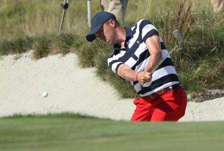 Oct 1, 2017; Jersey City, NJ, USA; Justin Thomas hits out of the sand on the ninth hole during the final round singles matches of The President's Cup golf tournament at Liberty National Golf Course. Mandatory Credit: Bill Streicher-USA TODAY Sports