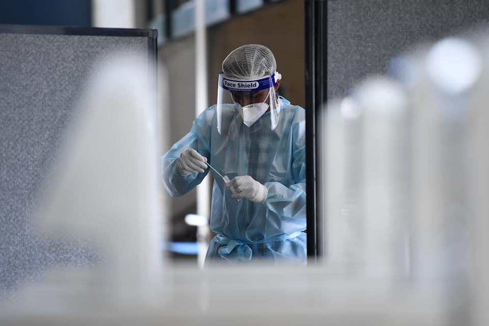 A healthcare worker handles a cover swab at a pop-up testing facility at the MCG stadium in Melbourne.