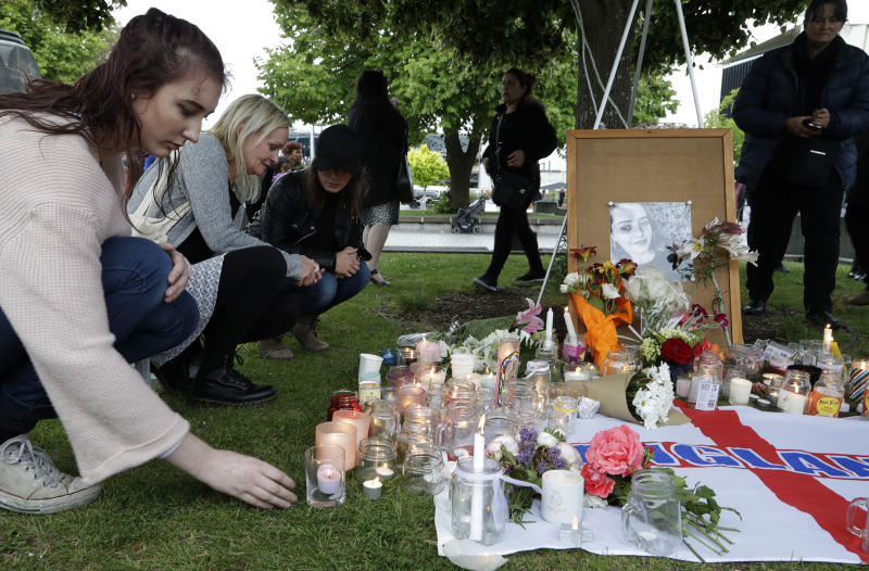 FILE - In this Dec. 12, 2018, file photo, people lay flowers and light candles during a candlelight vigil for the murdered British tourist Grace Millane at Cathedral Square in Christchurch, New Zealand. At a sentencing hearing at the Auckland High Court on Friday Feb. 21, 2020, the killer, who has name suppression, has been sentenced to life imprisonment with a minimum non-parole period of 17 years. (AP Photo/Mark Baker, File)