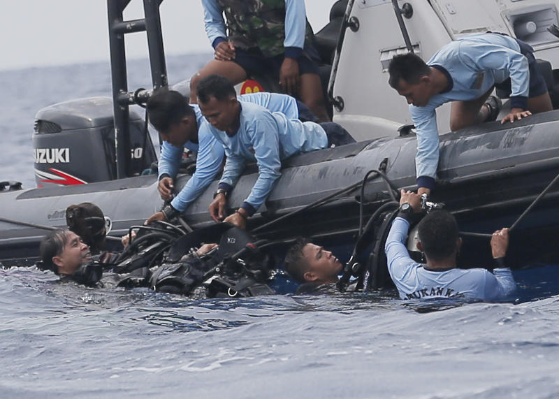 FILE - In this Oct. 30, 2018, file photo, Indonesian navy frogmen emerge from the water during a search operation for the victims of the crashed Lion Air plane in the waters of Tanjung Karawang, Indonesia. A search effort has located the cockpit voice recorder of the Lion Air jet that crashed into the Java Sea in October 2018, an Indonesian official said Monday, Jan. 14, 2019, in a possible boost to the accident investigation. Ridwan Djamaluddin, a deputy maritime minister, told reporters that the agency investigating the crash that killed 189 people had informed the ministry about the discovery. (AP Photo/Tatan Syuflana, File)