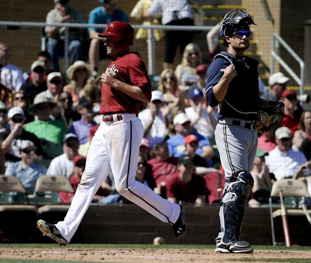Arizona Diamondbacks' A.J. Pollock, left, scores past Milwaukee Brewers catcher Jonathan Lucroy on a base hit by Gerardo Parra during the second inning of a spring exhibition baseball game in Scottsdale, Ariz., Sunday, March 16, 2014. (AP Photo/Chris Carlson)