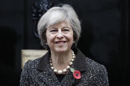 Britain's Prime Minister Theresa May poses with a poppy after buying it to mark this year's Poppy Appeal, at Number 10 Downing Street in central London