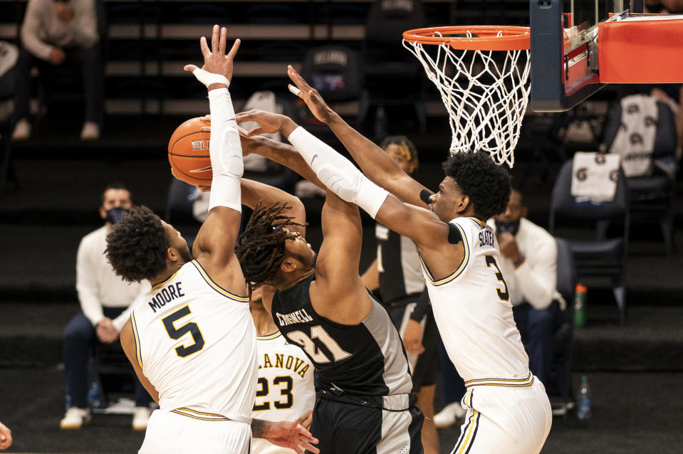 Villanova's Brandon Slater, right, and Justin Moore, left, defend the shot attempt by Providence's Ed Croswell, center, during the first half of an NCAA college basketball game, Saturday, Jan. 23, 2021, in Villanova, Pa. (AP Photo/Chris Szagola)