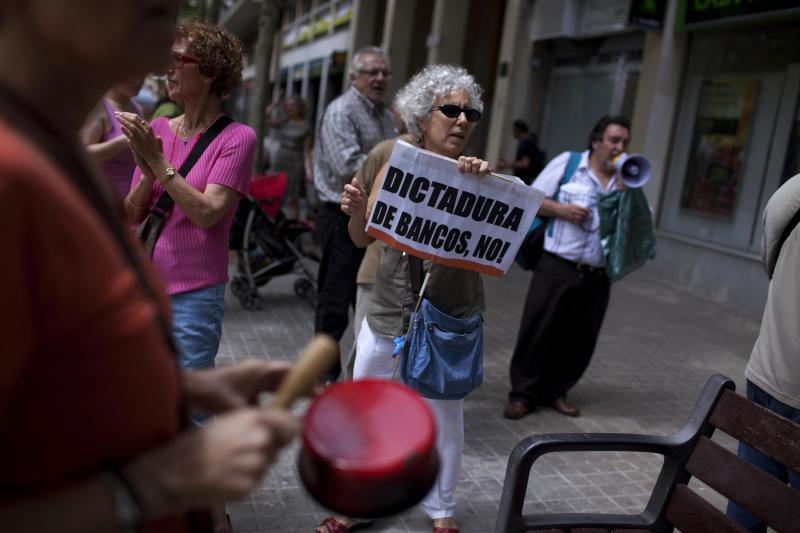 """Demonstrators shout slogans against bankers during a demonstration outside a Bankia bank branch in Barcelona, Spain, Friday June 8, 2012. Spain faces rising pressure to find a financial lifeline for its deeply troubled banks — likely from the eurozone's rescue fund since Madrid's borrowing costs on markets have risen sharply. The banner in Spanish reads """"No banks dictatorship"""". (AP Photo/Emilio Morenatti)"""