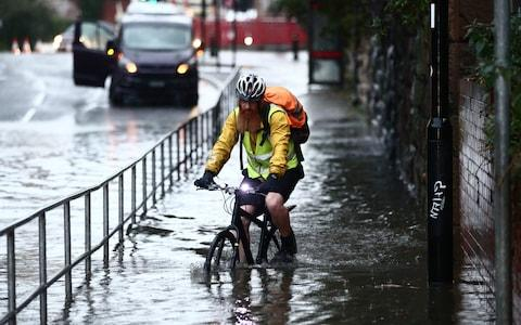 A man cycles through a flooded street Sheffield - Credit: Danny Lawson