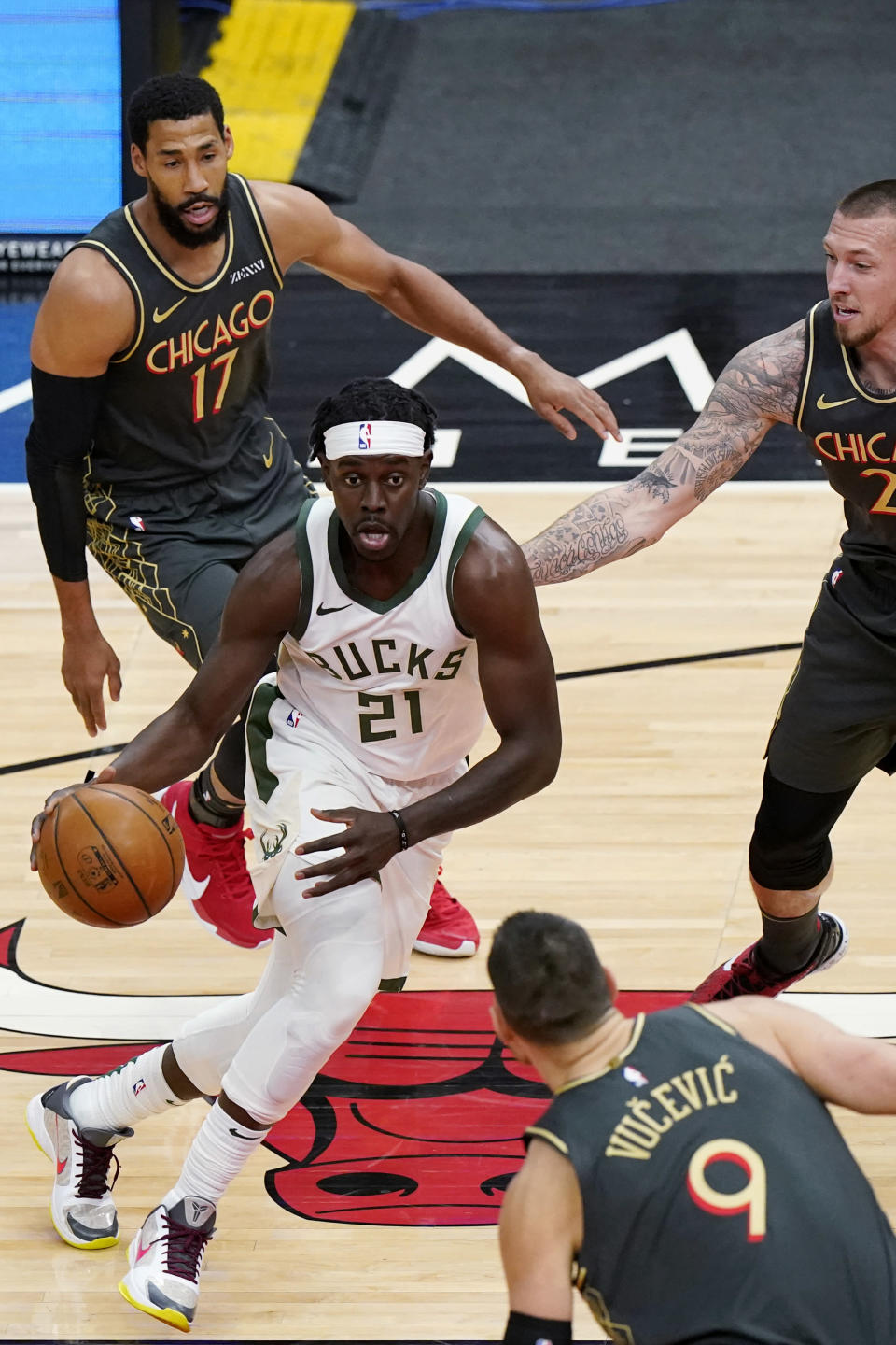 Milwaukee Bucks guard Jrue Holiday (21) drives against Chicago Bulls forward Garrett Temple (17), center Daniel Theis (27) and center Nikola Vucevic (9) during the first half of an NBA basketball game in Chicago, Friday, April 30, 2021. (AP Photo/Nam Y. Huh)