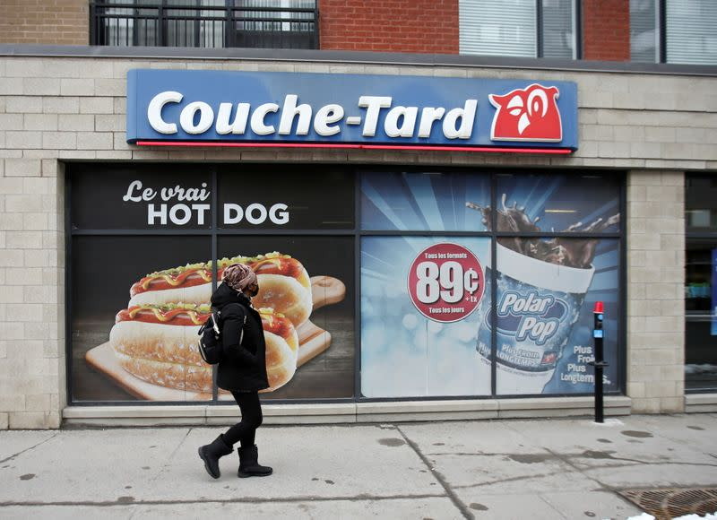 A pedestrian walks past a Couche-Tard convenience store in Montreal