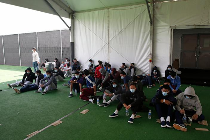 Minors who tested positive for Covid-19 sit on the ground at the Department of Homeland Security holding facility run by the Customs and Border Patrol (CBP) on March 30, 2021 in Donna, Texas. The Donna location is the main detention center for unaccompanied children coming across the U.S. border in the Rio Grande Valley. The children are housed by the hundreds in eight pods that are about 3,200 square feet in size. Many of the pods had more than 500 children in them. The youngest of the unaccompanied minors are kept separate from the rest of the detainees. The Biden administration has just allowed journalists inside its main detention facility at the border for migrant children. It is an overcrowded tent structure where more than 4,000 kids and families are kept in pods, with the youngest kept in a large play pen with mats on the floor for sleeping. (Photo by Dario Lopez-Mills - Pool/Getty Images)