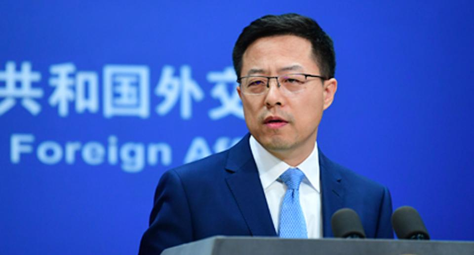Zhao Lijian wearing a navy suit and blue tie with glasses at a Foreign Ministry press conference.