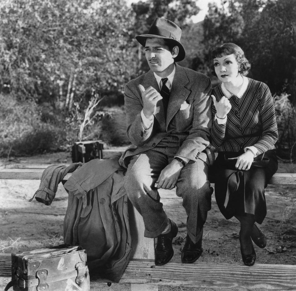 """(Original Caption) Clark Gable and Claudette Colbert try to get a lift in the great Frank Capra comedy """"It Happened One Night,"""" which won the 1934 Academy Award for best picture, best actor (Clark) and best actress (Claudette). Movie still."""