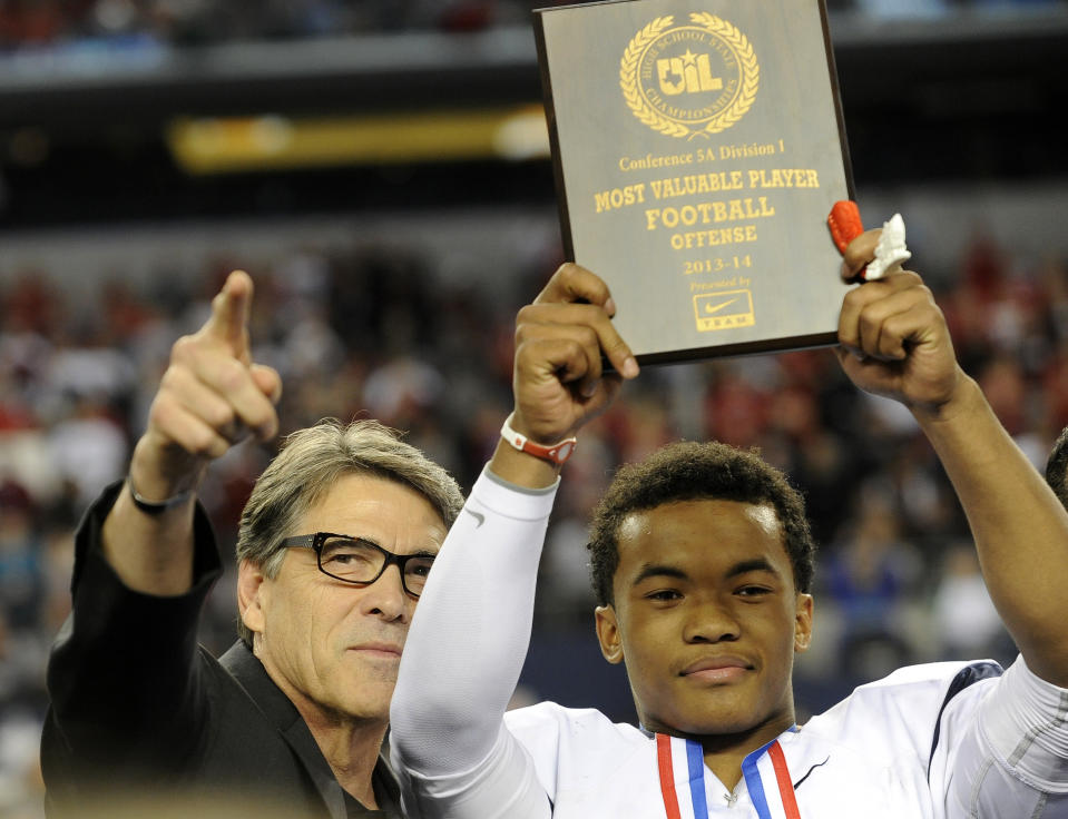 FILE - In this Dec. 21, 2013 file photo, Texas Gov. Rick Perry, left, poses for photos with the most valuable player,  offensive, Allen quarterback Kyler Murray, following a 63-28 win over Pearland during a UIL Class 5A  Division I high school football championship game in Arlington, Texas. Murray, who has a 41-0 record as the starter and is trying to win a third straight state championship, is the Texas Associated Press Sports Editors Player of the Year.  (AP Photo/Matt Strasen, File)
