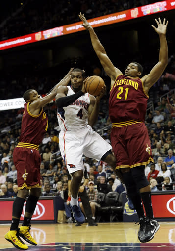 Atlanta Hawks power forward Paul Millsap (4) drives between Cleveland Cavaliers' C.J. Miles, lfet, and Andrew Bynum (21) in the first half of an NBA basketball game Friday, Dec. 6, 2013, in Atlanta. (AP Photo/John Bazemore)