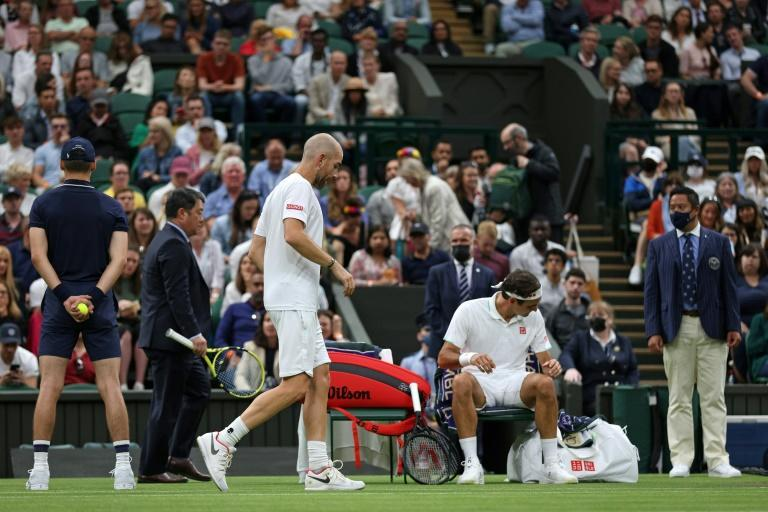 Almost over: Adrian Mannarino limps back to his chair during his defeat to Roger Federer