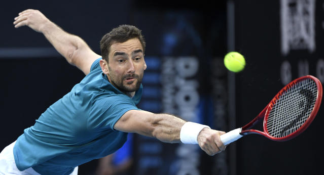 Croatia's Marin Cilic makes a backhand return to Spain's Roberto Bautista Agut during their third round singles match at the Australian Open tennis championship in Melbourne, Australia, Friday, Jan. 24, 2020. (AP Photo/Andy Brownbill)