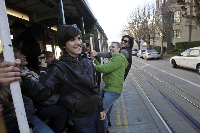 FILE - In this file photo from Jan. 21, 2011, from left, Franco Garavanno, Gustavo Ferrari and German Garavanno, who are visiting from Buenos Aires, ride a cable car up Hyde Street in San Francisco. In this city of innumerable tourist attractions, the clanging cable cars stand out as a top draw. They also stand out for the inordinate number of accidents and the millions of dollars annually the city pays out to settle lawsuits for broken bones, severed feet and bad bruises caused when 19th Century technology runs headlong into 21st Century city traffic and congestion.  Recently, five passengers and two workers were injured after an inch-long bolt in the track caused their cable car to slam to a sudden stop.  (AP Photo/Marcio Jose Sanchez)