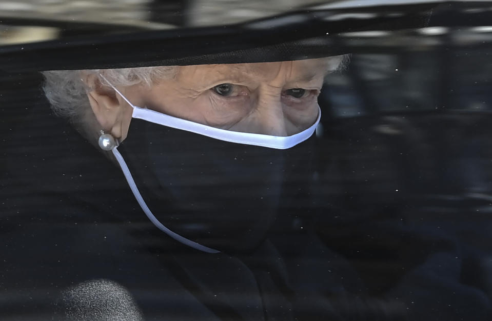 Britain's Queen Elizabeth II follows the coffin in a car as it makes it's way past the Round Tower during the funeral of Britain's Prince Philip inside Windsor Castle in Windsor, England Saturday April 17, 2021. (Leon Neal/Pool via AP)