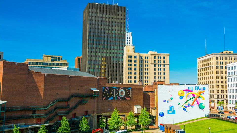 """Akron, United States - May 29, 2014:  Downtown Akron skyline with the words """"Akron""""on a sign in the center, and a colorful mural to the right."""