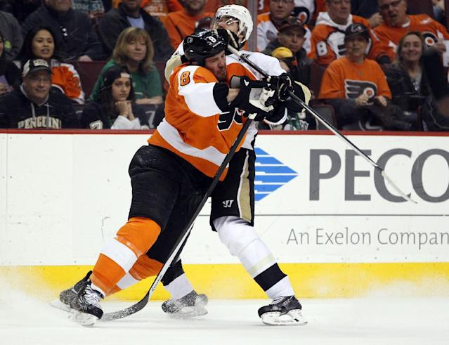 Philadelphia Flyers' Nicklas Grossmann, left and Pittsburgh Penguins' Evgeni Malkin collide along the boards during the first period of an NHL hockey game, Saturday, March 15, 2014, in Philadelphia. (AP Photo/Tom Mihalek)