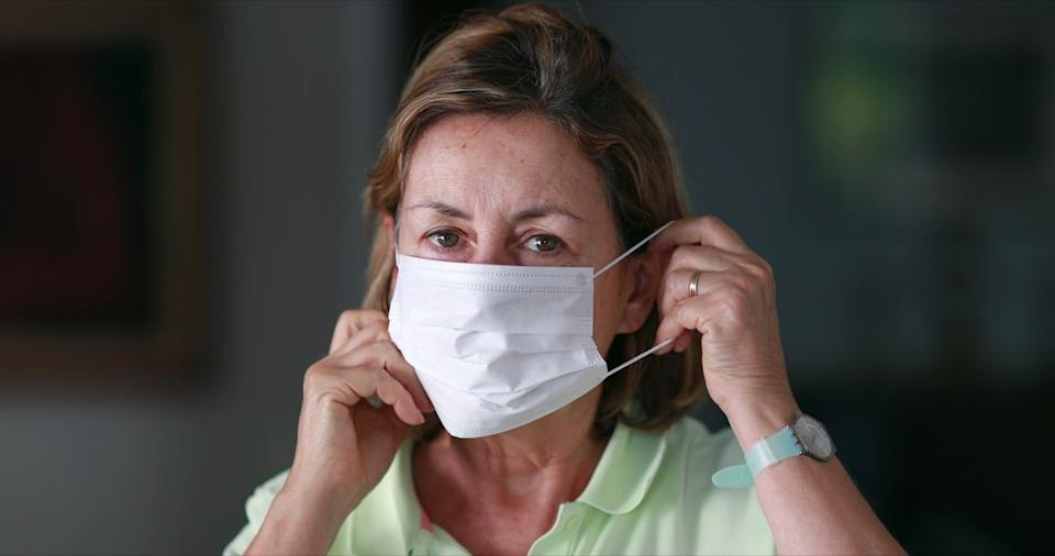 Senior woman putting on face mask protection.