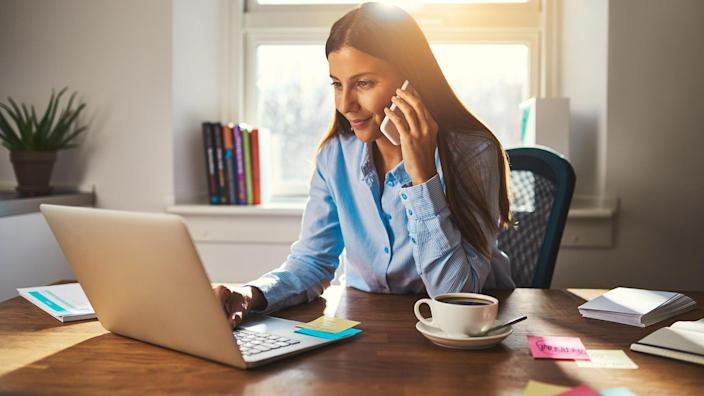 woman working at home and talking on phone