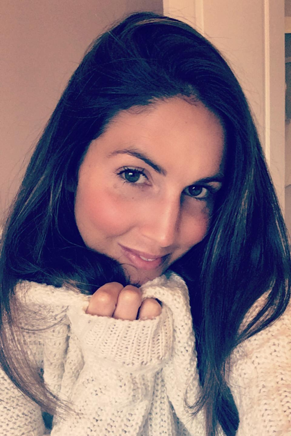 Anna Timson, a UK woman who went through early menopause aged 17, wearing a white knitted jumper